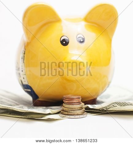 Yellow piggy bank and Stack of money coins isolated over the white background lot dollar cash under it close up