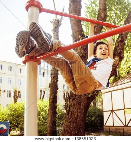 little cute blond boy hanging on playground outside, alone training with fun, lifestyle children concept close up