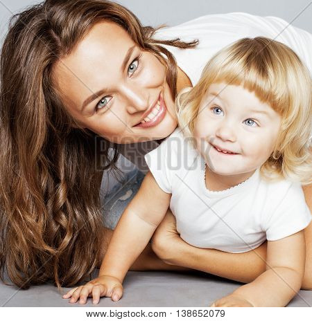 young pretty stylish mother with little cute blond daughter hugging, happy smiling family, lifestyle people concept close up