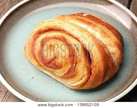Delicious pastry with cinnamon on a blue rustic plate