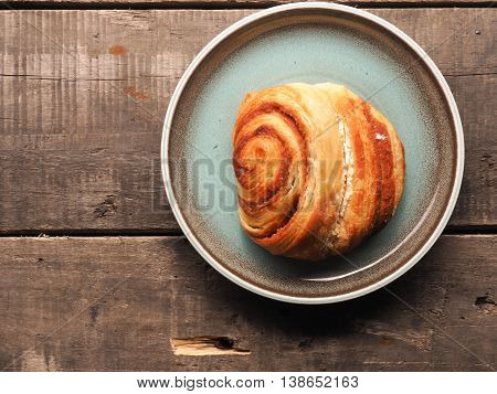 Delicious cinnamon pastry on a blue plate with space for text on the wooden background