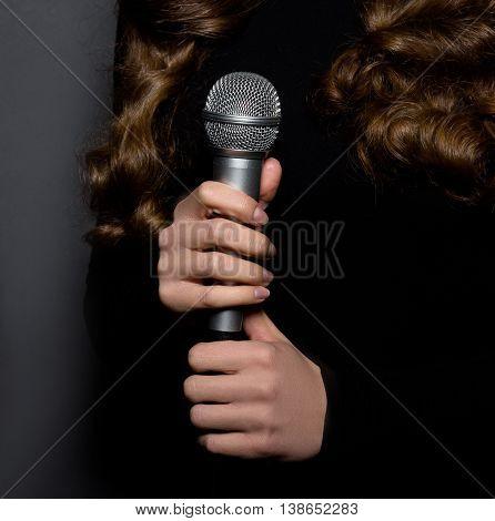 Closeup portrait of microphone. Beautiful lady singing in studio. Lady in black dress. Studio shot. Karaoke. Music concept.