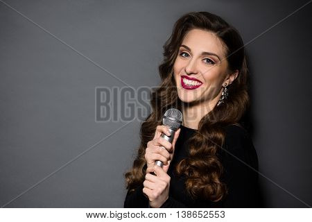 Portrait of beautiful lady with red lips singing in studio. Happy lady with long brown hair toothy smiling over grey background.