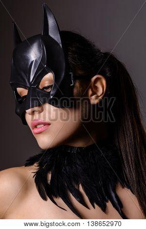 Portrait of charming brunette girl in Batman mask on a gray background