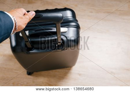 hand man in a suit holding a black suitcase handle