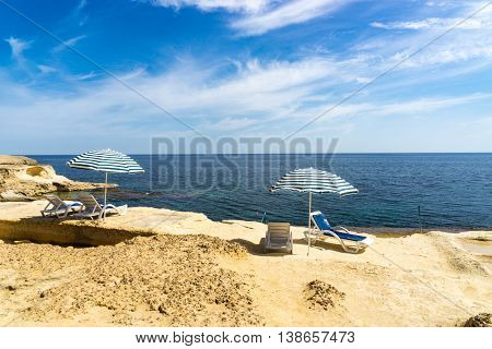Sun loungers on a beach underneath a parasol overlooking the Mediterranean sea