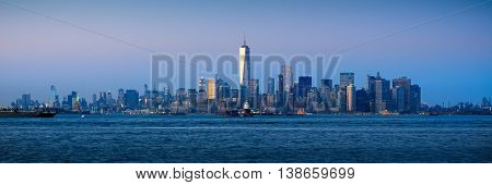 Panoramic Lower Manhattan Financial District skyscrapers and New York City Harbor at twilight
