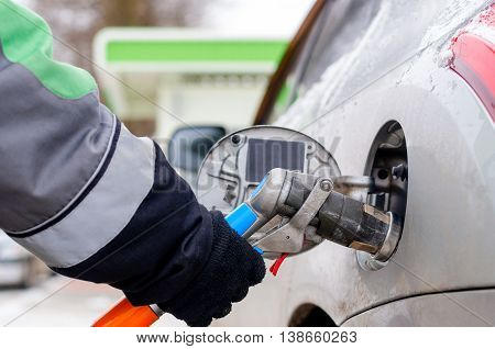 Fuel nozzle to refill fuel in car at gas station winter weather