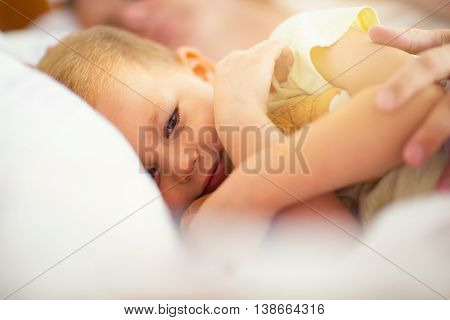 Time for bed! The little boy lying in bed hugging a toy father sleeping behind him selective focus