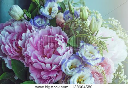 Rich bunch of pink peonies peony and lilac eustoma roses flowers, green leaf on blue background with sun light. Spring or summer lovely bouquet. Love concept. Card, text place, copy space. Wallpaper