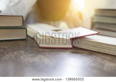 Confused And Frustrated Man With Textbook Stack On Wooden Desk