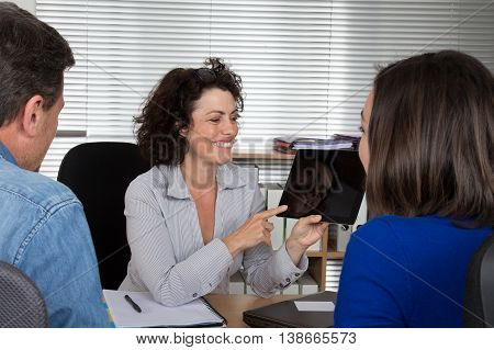 Realestate Agent With Couple Interested To Invest In House On Tablet