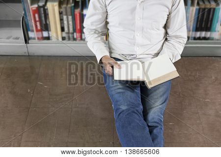 Man Reading Book In Aisle In Library
