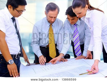 Business men and women working on blue prints