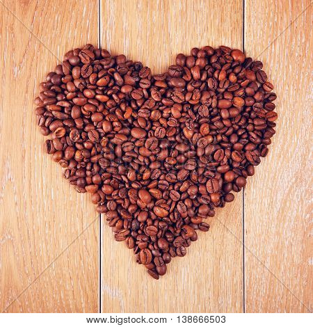 coffee beans in shape of heart on wooden table, background