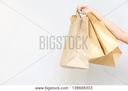 Close up of female hand holding shopping packets. Isolated and copy space in left side