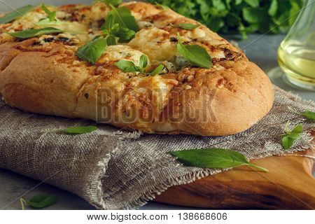 Focaccia with onions herbs and cheese garnished with basil leaves.