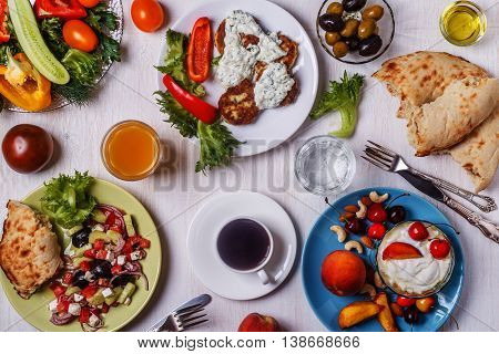 Greek appetizers - fritters of zucchini with tzatziki sauce Greek salad yogurt with fresh fruit and nuts olives vegetables and herbs top view.