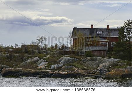 Old traditional red wooden house on the rocky shore in archipelago of Helsinki, Suomenlinna