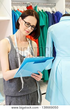 Skillful fashion designer is drawing sketch of clothing with inspiration. She is standing near mannequin in atelier and holding folder. Woman is smiling