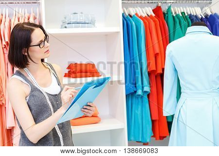 Smart female tailor is working in atelier. She is compering new dress on mannequin with sketch. Woman is standing and looking at clothing pensively