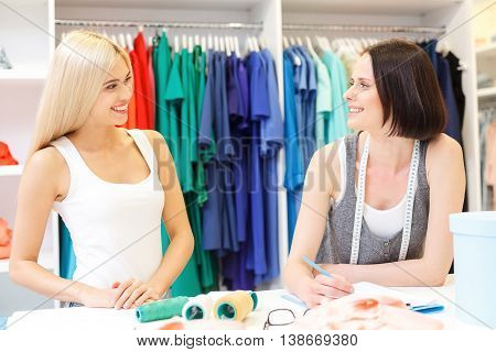 Talented female dressmaker is serving her client. She is listening to woman attentively and smiling. Ladies are standing ad smiling in workshop