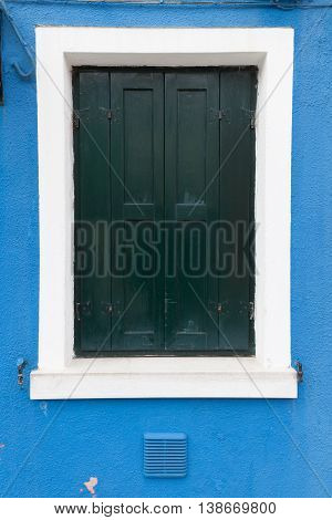 Picturesque old window with dark green shutters on blue wall (Burano island Venice Italy)