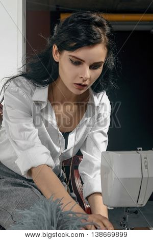 Girl Sews Clothes. She Is Dressed In A White Shirt