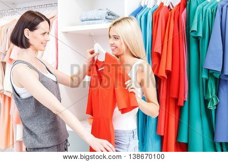 Cheerful young saleswoman is advising woman in boutique. She is holding dress near female body and looking at client with satisfaction. Blond girl is smiling
