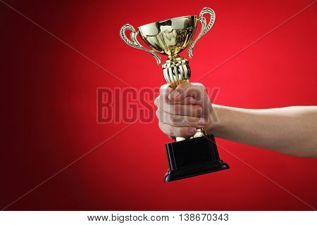 hand holding up a gold trophy cup on the res background