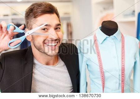 Talented young designer is working in atelier with joy. He is holding scissors near face and smiling. Man is standing near mannequin with female clothing