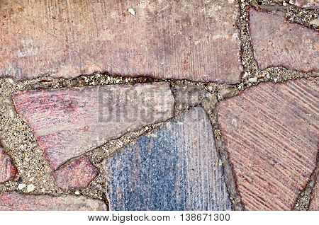 The wall, built of pieces of red granite of various sizes, reinforced cement
