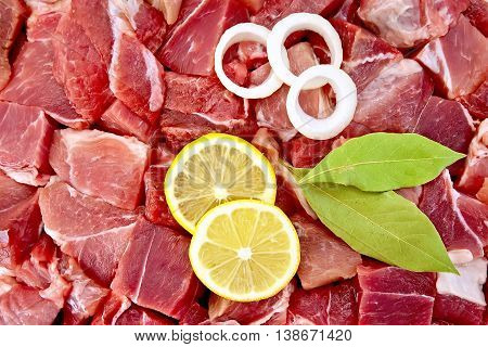 Texture of pieces of raw meat with bay leaf, rings of white onion and lemon slices