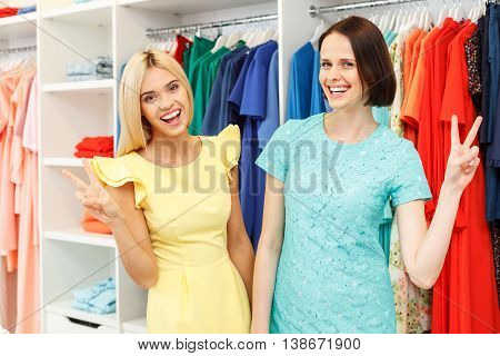 Happy young women are trying on new dresses in boutique. They are standing and smiling. Friends are looking at camera and showing peace sign