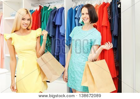 Fashionable two women are going shopping with joy. They are standing in boutique and holding packets. Friends are looking at camera and smiling
