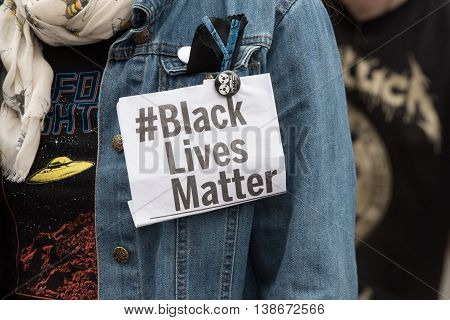 Liverpool, UK: July 16, 2016: A marcher wears a label protesting Black Lives Matter during a march in solidarity in Liverpool to the Black Lives Matter movement.