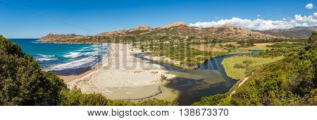 Panoramic view of Ostriconi beach and the Desert des Agriates in the Balagne region of Corsica showing the lush green river valley and Etang de Foce with clear blue skies overhead