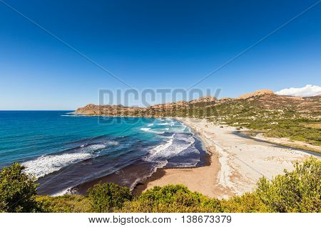 View of Ostriconi beach and the Desert des Agriates in the Balagne region of Corsica showing the lush green river valley behind the beach with clear blue skies overhead