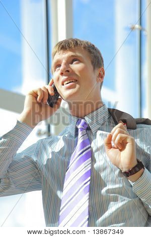 Portrait of happy businessman talking on mobile in office lobby