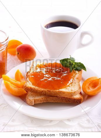 Apricot jam over toasts on plate and coffee