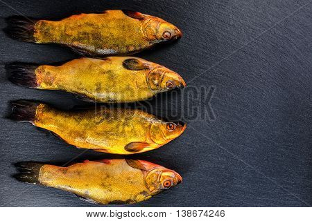 flat lay of fresh tench fish on slate background close up