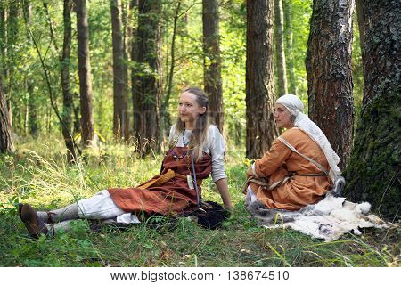 Gnezdovo, Russia - August 09, 2014, Two girls in the ancient Russian clothes sitting on the grass during the festival of historical reconstruction