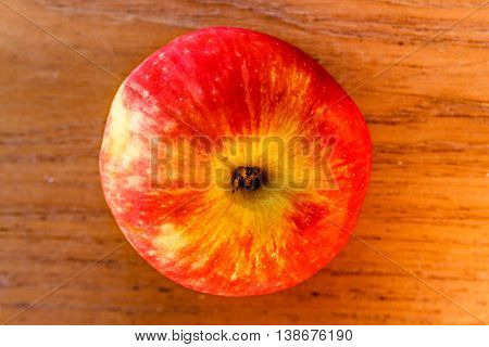 Whole not peeled apple on wooden board