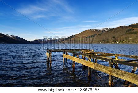Decaying jetty on loch in Central Scotland.