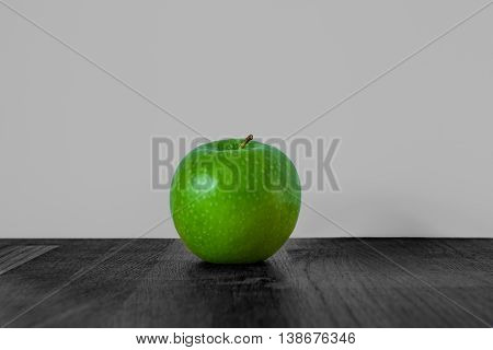 Green apple in high contrast black and white background