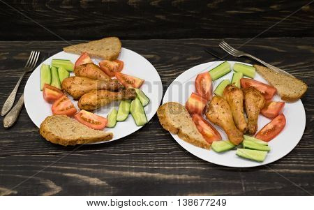 Grilled chicken legs and vegetables on the plate on a wooden background. Fork Knife