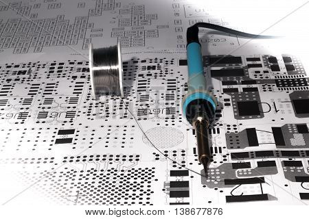 soldering iron placed with lead wire on electronic layout