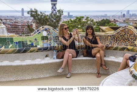 BARCELONA SPAIN - JULY 3 2016: Women are sitting on a bench in the Park Guell. Park Guell is the famous architectural town art designed by Antoni Gaudi and built in the years 1900 to 1914