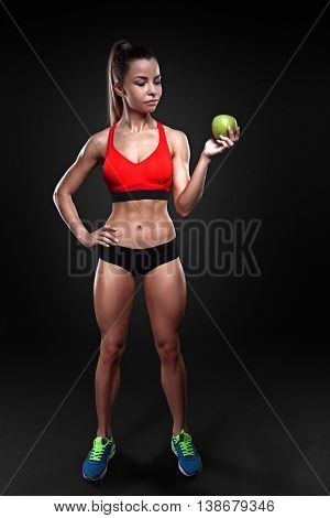 Beautiful sportly fitness woman holding an apple. Anti-cellulite program. Heatly nutrition and eating. Dieting.