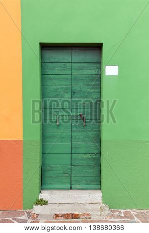 Old wooden green locked door with peeling paint in the green wall (Burano island Venice Italy)